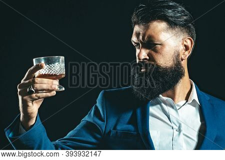 Confident Well-dressed Man With Glass Of Whisky. Serious Sad Woman Having Alcohol Addiction. Man Dri