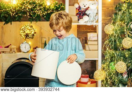 Happy Little Boy Child With Present Or Gift Box Indoors. Happy Cute Child In Santa Hat With Present