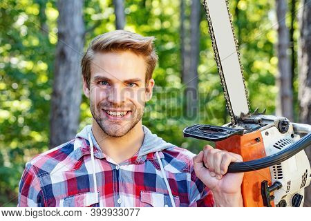 Strong Lumberjack With Chainsaw In A Plaid Shirt. Lumberjack Worker Walking In The Forest With Chain
