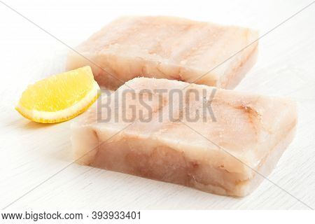 Two Quick Frozen Pollock Fillet Blocks With A Lemon Wedge Isolated On White.