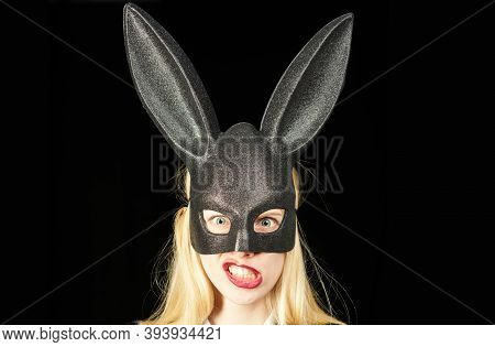 Sexy Woman With Mask Easter Bunny On A Black Background And Looks Very Sensually. Closeup Of Winking