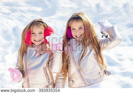 Little Girls Throw Snowball In Park. Portrait Of Two Little Girls Play With Snow In Winter. Cute Sis