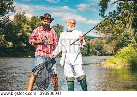 Generations Ages: Grandfather And Father. Grandfather And Boy Fishing Together. Happy Grandfather An