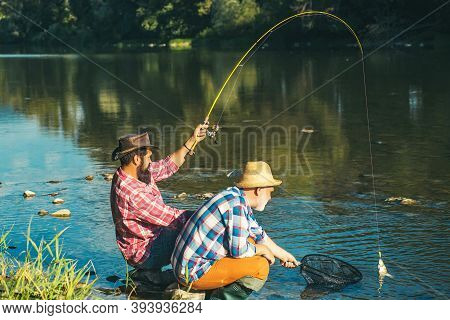 Man Fisherman Catches A Fish. Fly Fishing Is Most Renowned As A Method For Catching Trout Grayling A