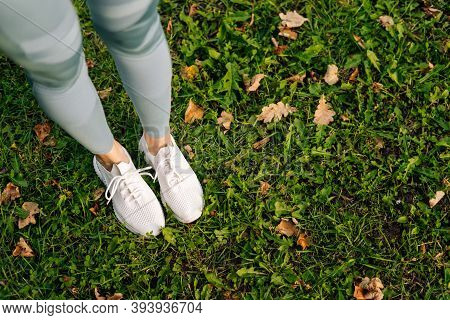 Close-up Of Unrecognizable Woman Feet In White Sneakers Standing And Poses In Place On Green Grass.