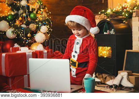 Santa Helper Using Notebook. Child Type Letter To Santa. Portrait Of Cute Dreamy Santa Helper Writin