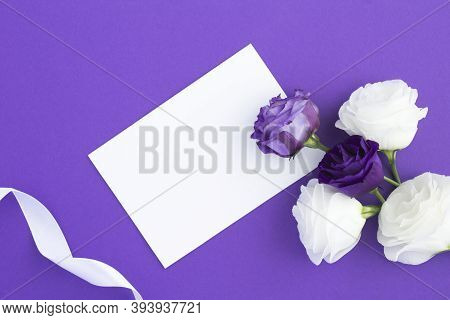 Top View Of Empty White Paper For Text, Violet And White Flowers On The Violet  Background