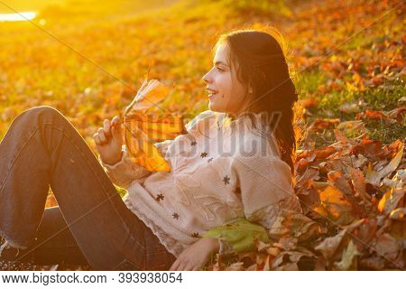 Woman Enjoy Autumn. Girl Relaxed Lay Fallen Leaves On Sunny Autumn Day. Warmth And Coziness. Female