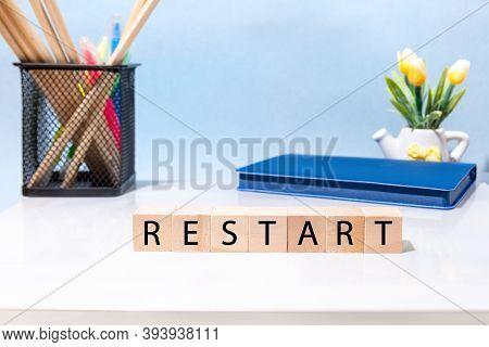 The Word Restart Is Written On Wooden Blocks On The Desktop In The Office. Restarting Business, Work