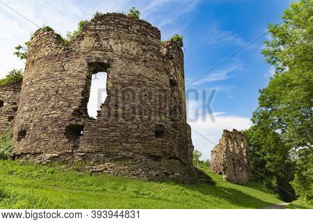 Scenic Ruins Of The Buchach Medieval Castle Among Bright Green Plants At The Cloudy Sky Background.