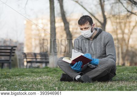 The Man In Protective Mask And Gloves Is Reading Book And Sitting On The Grass Outdoors.