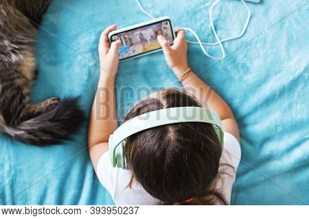 Child With Headphones Playing A Computer Game On The Phone, The Cat Is Sleeping. A Little Girl Lies