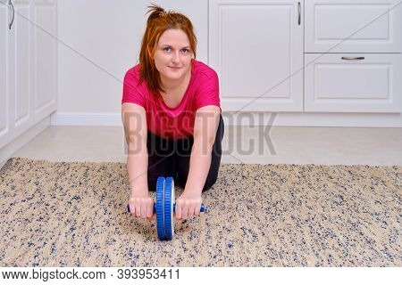 A Woman Does A Press Exercise In The Home Room. Woman With A Blue Roller To Strengthen The Press On