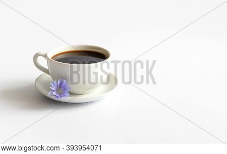 Chicory Beverage In A Small Cup And A Blue Chicory Flower Isolated On A White Background. Coffee Sub