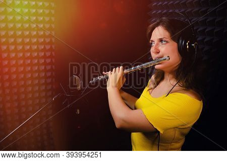 Woman Flutist Playing The Silver Flute. Record Wind Musical Instruments With A Professional Micropho