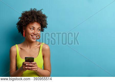Horizontal Shot Of Pretty Smiling Woman Types On Smart Phone, Waits For Call, Looks Away With Glad E