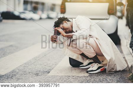 A Young Fancy Black Female Tourist In A White Stylish Trench Is Squatting On A Pedestrian Crossway,