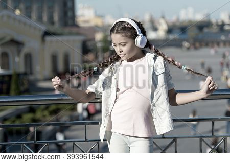 I Love My Pigtail Hairstyle. Small Child Wearing Braided Hairstyle And Headphones Outdoor. Little Gi