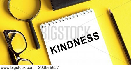 Kindness Is A Word Written In A Notebook On A Yellow Background With Glasses, A Magnifying Glass And