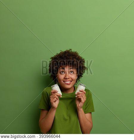 Pleased Dark Skinned Woman Holds Jars Of Organic Natural Yoghurt, Ingredient For Preparing Breakfast