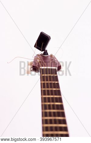 Guitar Tuner. Wooden Guitar On A White Background. Guitar Tuning.