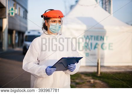 Paramedic Wearing Personal Protective Equipment Ppe Holding Folder Standing In Front Of Icu Hospital