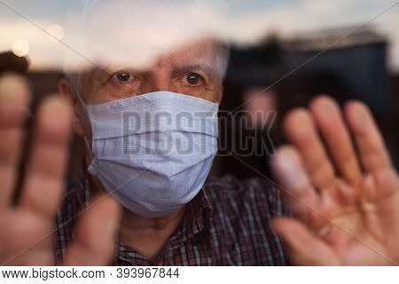 Elderly Caucasian Man Wearing Hand Made Protective Face Mask,in Nursing Care Home,looking Outside Wi