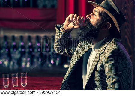 A Drink For The Man. Close Up Of A Man Drinking Whiskey At The Bar. Alcoholic With Serious Face Drin