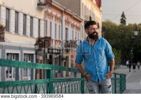 Portrait Of Fashionable Well Dressed Man With Beard Posing Outdoors Looking Away, Confident And Focu