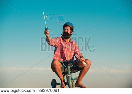 Funny Man On A Bicycle. Emotional Crazy Guy On A Childrens Bike. Funny Young Man With Motorbike Helm