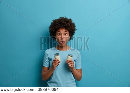 Scared Emotional Dark Skinned Woman Gasps From Shock, Keeps Jaw Dropped, Holds Two Glasses Of Yoghur