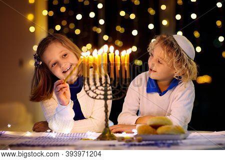 Kids Celebrating Hanukkah. Jewish Festival Of Lights. Children Lighting Candles On Traditional Menor