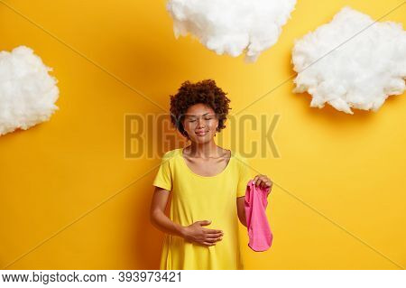 Pregnant Woman Cares About Future Child Touches Belly, Stands With Closed Eyes And Charming Smile, H