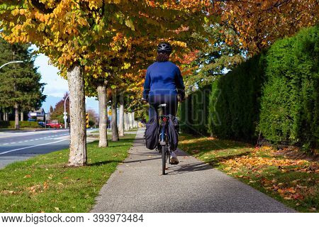 Girl Riding A Bicycle On A Sidewalk In A Calm Neighborhood. Taken In Fraser Heights, Surrey, Vancouv