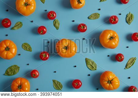 Ripe Fresh Red And Yellow Tomatoes Growned In Greenhouse, Basil Leaves And Peppercorn On Blue Backgr