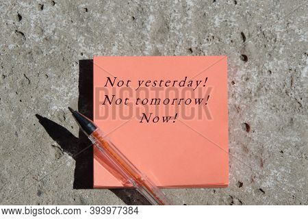 Not Yesterday! Not Tomorrow! Now!   Phrase On A Pack Of Stickers On A Concrete Surface