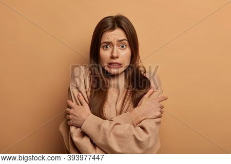 Image Of Young Woman Cannot Warm Herself, Trembles From Cold, Crosses Hands Over Body, Clatters Teet
