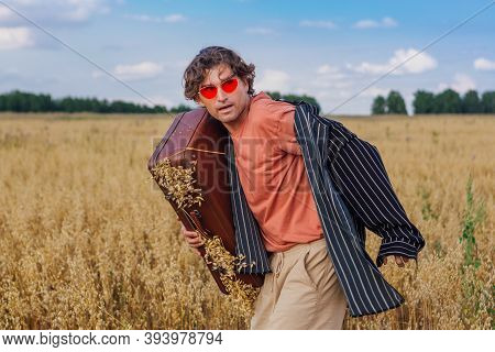 Tall Handsome Man With Brown Suitcase Full Of Ears Of Oats Standing At Golden Oat Field.