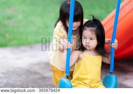 The Sisters Taught The Sisters To Play Swings. Two Child Girl Sisters Played Swings Together. The As