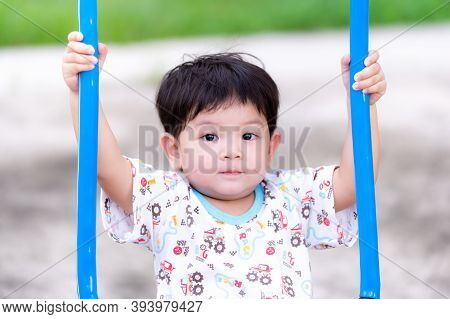 Snapshot Of An Asian Little Child Boy Holding A Blue Swing. Children Are Playing On The Playground I