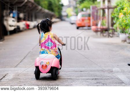 Back Side Of Little Daughter Driving An Electric Motorcycle For Toy Is Pink And White. Asian Girl Is