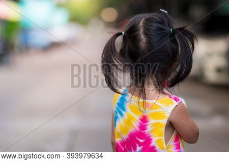A Black Haired Child Girl Stood With Her Back With Camera. Asian Girl Tied Two Hairs. Show A Beautif