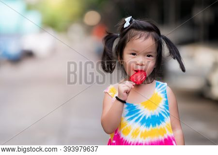 One Cute Little Child Girl Eating Red Popsicle Sticks. Asian Children Stroll In The Summer Evening O