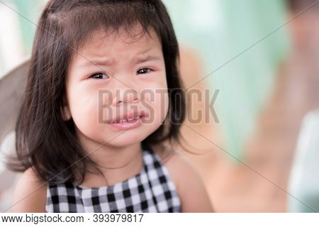 Head Shot Of Asian Cute Girl Is Crying Self-indulgent For Some Dissatisfaction.kid Looks At Camera.