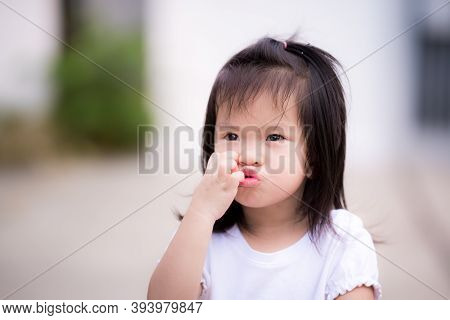 Happy Girl Is Using Her Hand Scratching Her Face And Making A Puckered Up Mouth In A Good Mood. Chil