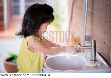 Asian Girl Stands To Washing Hands. Kid Rubbed Both Hands With Soap Bubble. Child Use Right Hand To