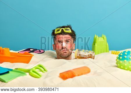 Head Of Man With Thoughtful Expression, Buried In Sand, Drinks Refreshing Beverage, Uses Sunblock, S