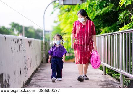 Family Wear Cloth Masks. Mother Carrying Pink Of Daughter Mattress Bag Went To School. Families Prot