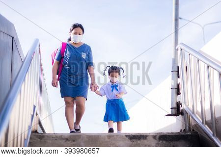 Mother And Daughter Wear Cloth Masks. Two Of Them Walked Hand In Hand, Walking Down The Steps Of Ove
