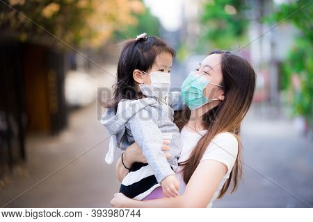 Family Carried Child. Mother And Daughter Wear Medical Face Mask. Mom Smiled At Little Girl. Concept